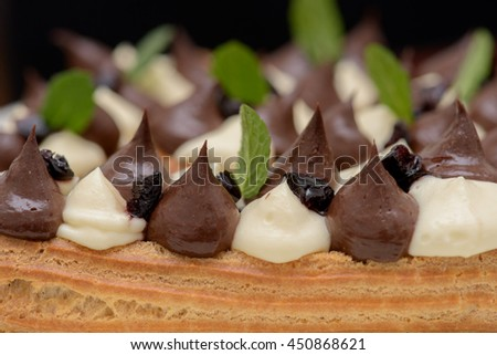 Eclairs with chocolate custard and whipped cream and mint leaves