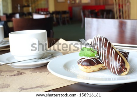 Eclairs with cream in chocolate coating on a plate and tea in cafe - stock photo