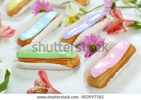 Eclairs with glaze on a white wooden table - stock photo