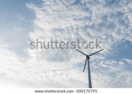 Eclectic wind power turbine on blue sky - stock photo