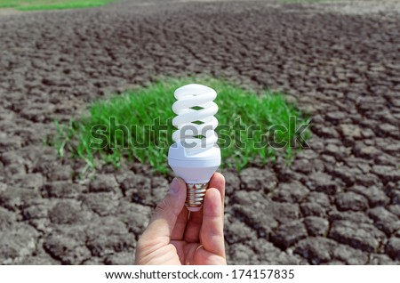 eco bulb in hand over desert and green grass - stock photo