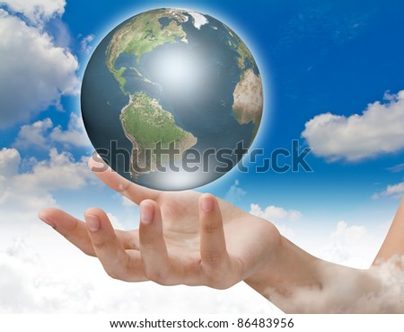 Eco concept : Earth in hands over blue sky - stock photo