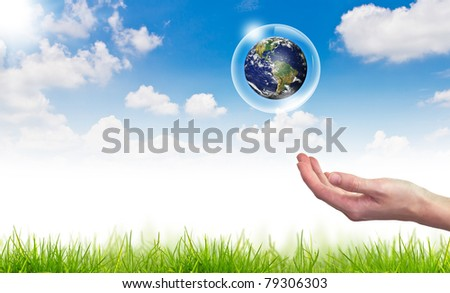 Eco concept : Hand hold  globe  in bubbles against the sun and the blue sky - stock photo