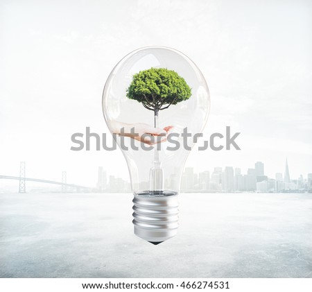 Eco concept idea with hand holding tree inside abstract lightbulb on foggy city background. 3D Rendering