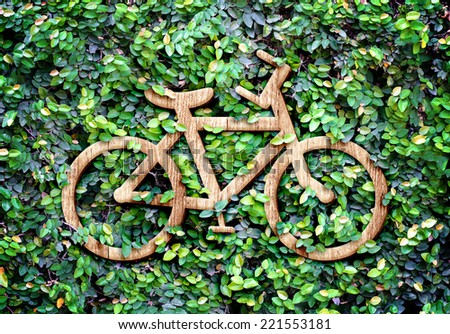 Eco concept :Wood texture Bicycle  icon on green leaves wall - stock photo