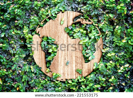 Eco concept :Wood texture world icon on green leaves wall - stock photo