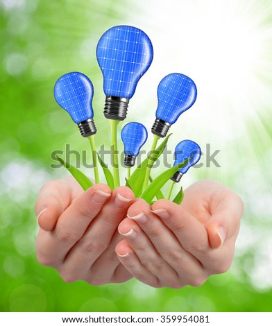 Eco energy light bulbs in hands on green natural background - stock photo