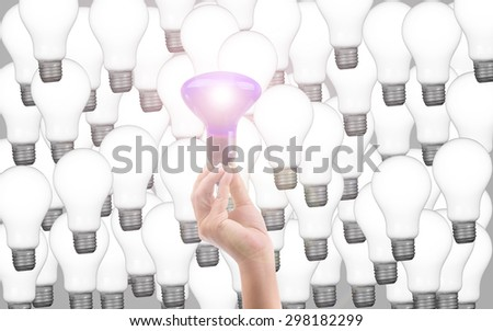 Eco energy saving light bulb , one glowing compact fluorescent lightbulb standing amongst the unlit incandescent bulbs with reflection - stock photo