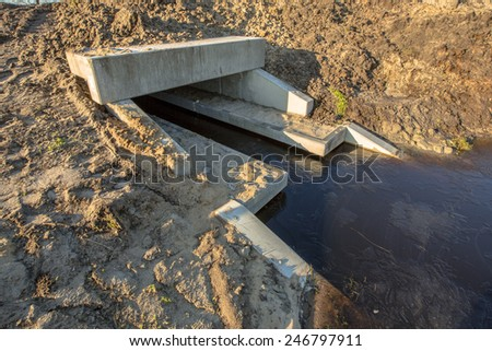 Eco Friendly Culvert under construction with walking strips for animals above the waterline serving as a wildlife crossing - stock photo