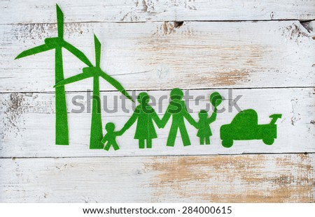 Eco friendly family. Go green concept. Happy paper family  standing near wind farm on wooden background - stock photo