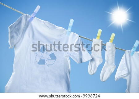 Eco- friendly  laundry drying on clothes line against a blue sky with sun - stock photo