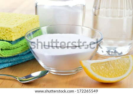 Eco-friendly natural cleaners. Vinegar, baking soda, salt, lemon and cloth on wooden table. Homemade green cleaning. - stock photo