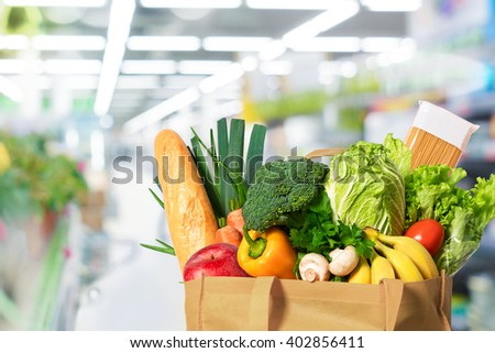 Eco friendly reusable shopping bag filled with vegetables on th supermarket background