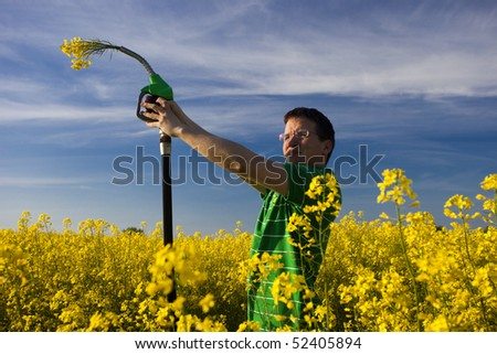 Eco fuel concept: young man in nature with gas station nozzle with flowers - stock photo