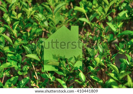 Eco house concept in a green plants , green eco house icon in nature - stock photo