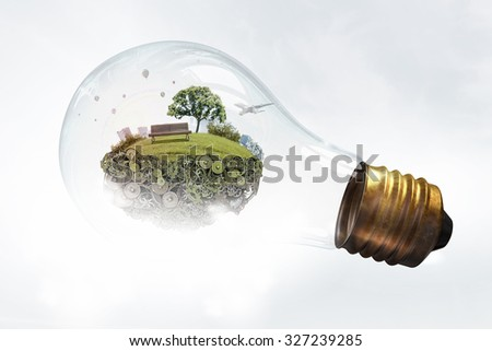 Eco life and energy saving concept in glass light bulb - stock photo