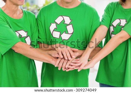 Eco-minded colleagues putting hands together in the office - stock photo