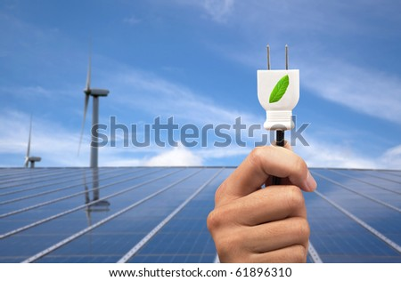 eco power concept.hand holding green power plug and solar panel and wind turbine background - stock photo