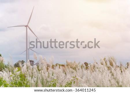 Eco power in wind turbine farm with flowers. - stock photo