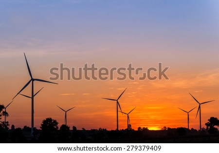Eco power in wind turbine farm with sunset.