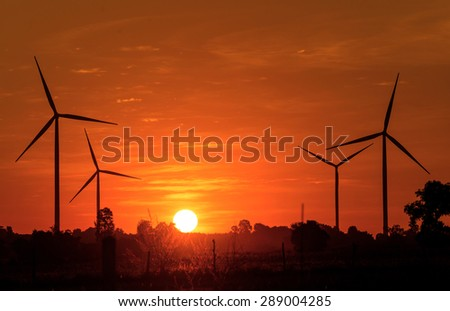 Eco power in wind turbine farm with sunset. - stock photo