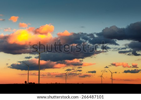 Eco power, wind turbines in orange sunset - stock photo