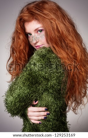ecoist young ginger lady with green freckles on her face looking at camera - stock photo