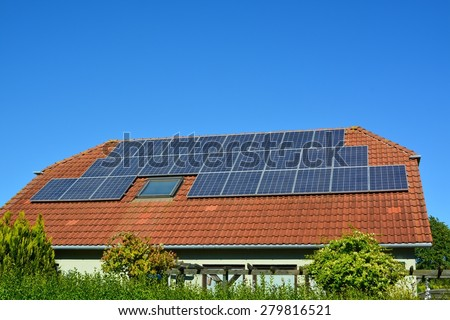 Ecological and renewable solar energy panels on the roof of a house - stock photo