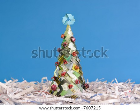 Ecological christmas tree made of newspaper cuttings with recycle three-arrow symbol on top over blue background - stock photo