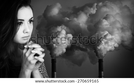 Ecological concept. Black and white image of young woman prays against the background of pipes polluting an atmosphere - stock photo