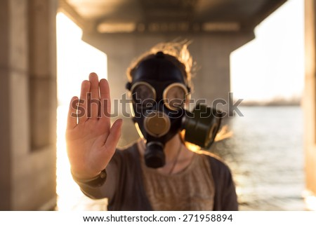 Ecological concept of air contamination. Woman in gas mask near water showing stop gesture