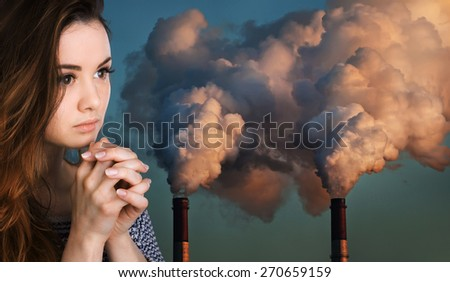 Ecological concept. Young woman prays against the background of pipes polluting an atmosphere - stock photo