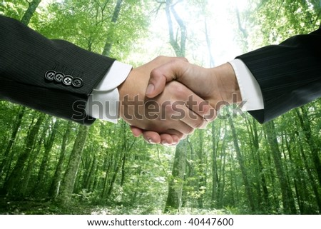 Ecological handshake businessman in a forest green background [Photo Illustration] - stock photo