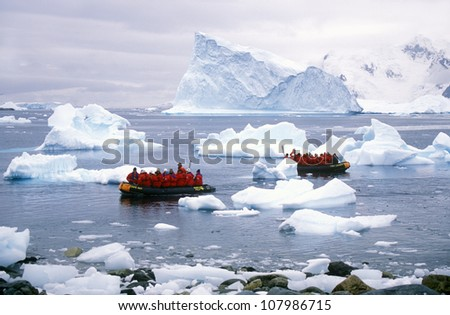 Ecological tourists in inflatable Zodiac boat observe Gentoo penguins in Paradise Harbor, Antarctica