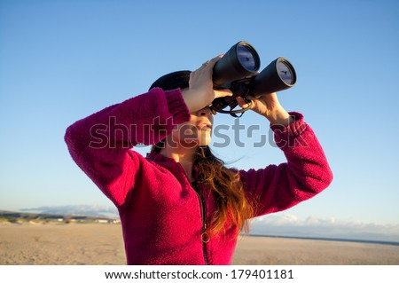 Ecologist young woman watching the environment birds on the coast with binoculars. Wide angle of view - stock photo