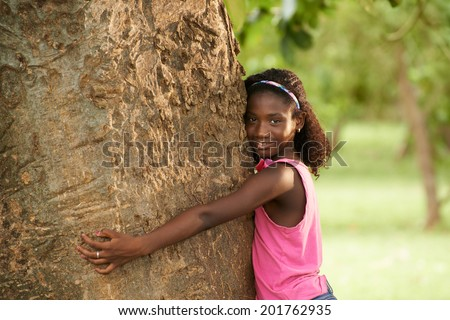 Ecology and environment-Portrait of young african american girl embracing and hugging tree in park, smiling and looking at camera - stock photo