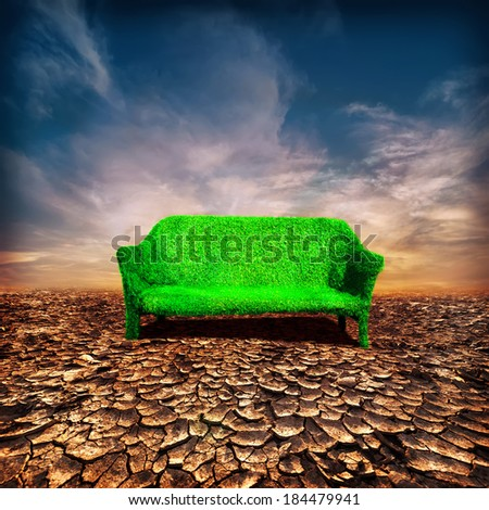 Ecology and global warming concept. Grassy sofa standing under cloudy dramatic sunset sky at drought cracked desert landscape - stock photo