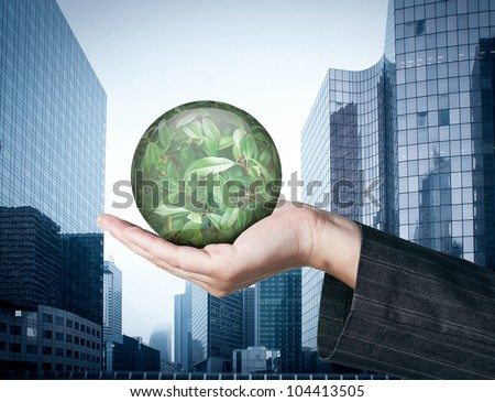 Ecology concept: Hand holding a globe with nature leaves on business buildings background - stock photo