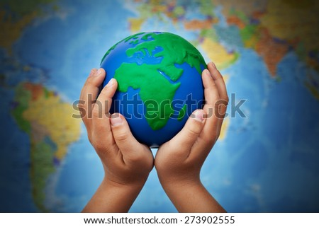 Ecology concept with earth globe in child hands against blurry world map - stock photo