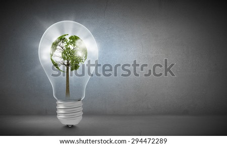Ecology concept with green tree inside of light bulb