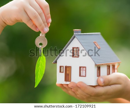 Ecology house and key in hands against green spring background