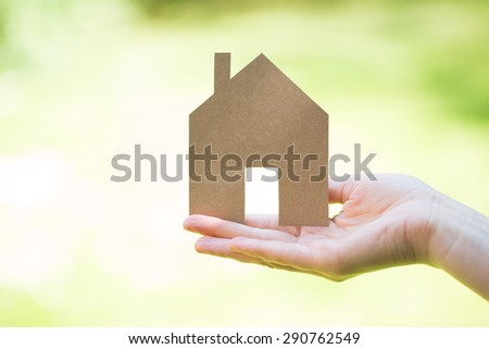 ecology idea - house cut of paper in woman hands - stock photo