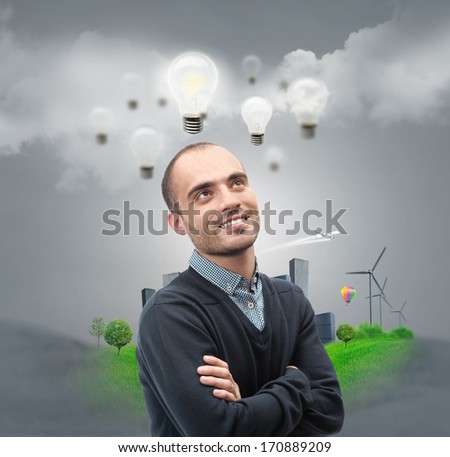 Ecology ideas concept. Businessman standing in front of cityscape with lamp overhead - stock photo