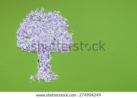 ecology recycle concept with big tree made from shredded white paper over green  - stock photo