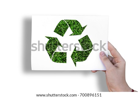 Ecology sign on white sheet on grass background in hand
