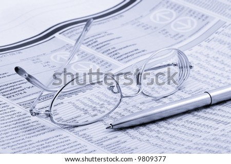 economic newspaper with glasses and pen - stock photo