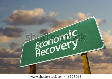 Economic Recovery Green Road Sign with dramatic clouds and sky. - stock photo