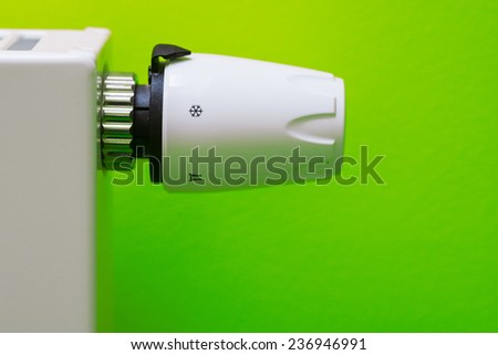 Economical thermostat setting - green background. Save energy and money concept - stock photo