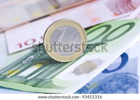 Economy concept with One Euro coin on Euro banknotes