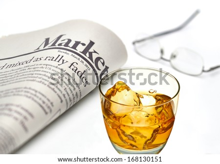 Economy newspaper with whiskey glass on white background in shallow depth of field - stock photo